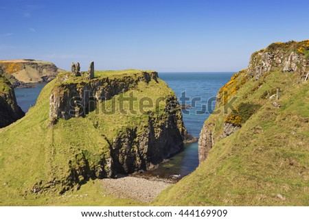 Cliffs with the ruins of Dunsverick Castle along the Causeway Coastal Way on the coast of Northern Ireland. Photographed on a bright and sunny day. - stock photo