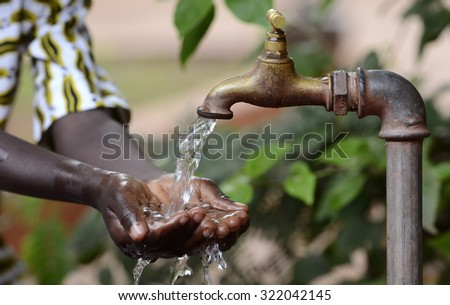 Climate Change Symbol: Handful Of Water Scarsity for Africa Symbol. Hand of an African black boy with water pouring from a tap.  - stock photo