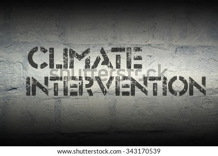 climate intervention stencil print on the grunge white brick wall - stock photo