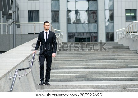 Climb to the the peak of success. Successful and confident businessman in formal attire goes down the stairs - stock photo