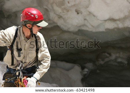 Climber above crevasse - stock photo