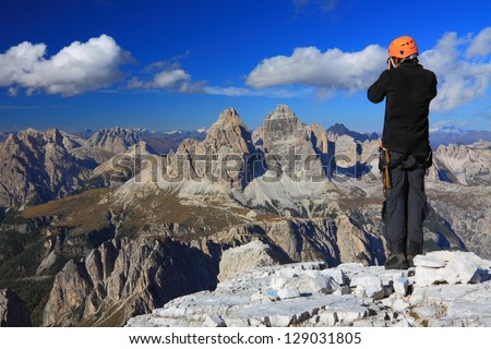 Climber admiring the view and taking pictures, Dolomite Alps, Italy - stock photo