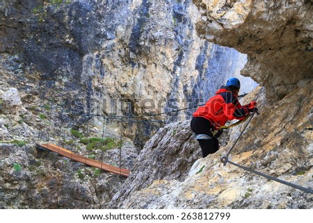 "Climber approaching suspension bridge between steep rock walls on via ferrata ""Brigata Tridentina"", Sella massif, Dolomite Alps, Italy - stock photo"