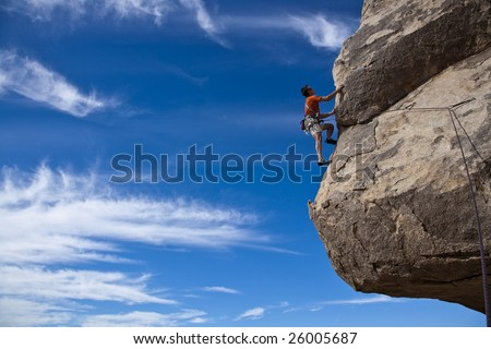 Climber ascends a steep, rock overhang in Joshua Tree National Park, California. - stock photo
