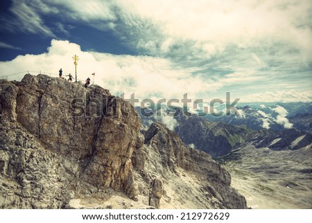 climber at the summit of the Zugspitze, at 2,962 meters above sea level, it is the highest peak of the Wetterstein Mountains as well as the highest mountain in Germany, Europe, vintage style - stock photo