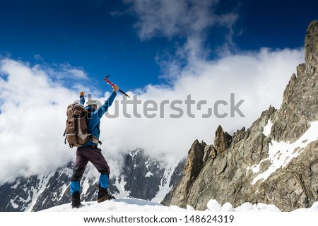Climber at the top of a rock with his hands raised enjoy sunny day  - stock photo