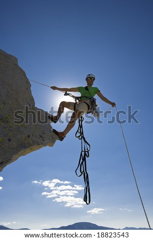 Climber beginning her descent from the summit of a rock spire in The Sierra Nevada Mountains, California, on a summer day. - stock photo
