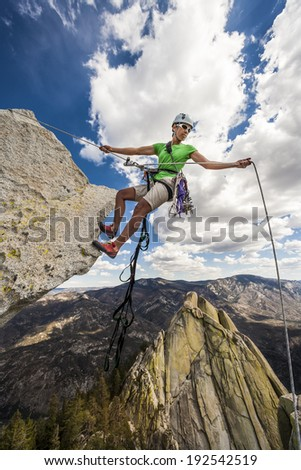 Climber begins her descent on the edge of a challenging cliff. - stock photo