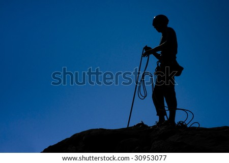 Climber belaying, (fast shutter freezing movement of the rope) - stock photo