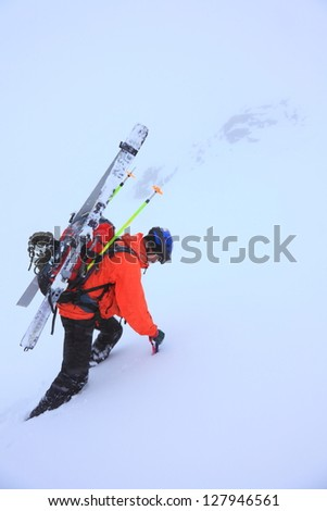 Climber carrying skies and ascending a snow covered mountain slope in bad weather - stock photo