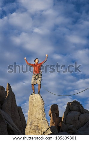 Climber celebrates on the summit of a rock spire. - stock photo