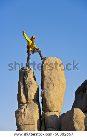 Climber celebrates on the summit of a rock spire in the Sierra Nevada Mountains, California, after a successful ascent. - stock photo