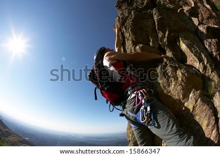 Climber climbing a rocky wall; horizontal frame - stock photo