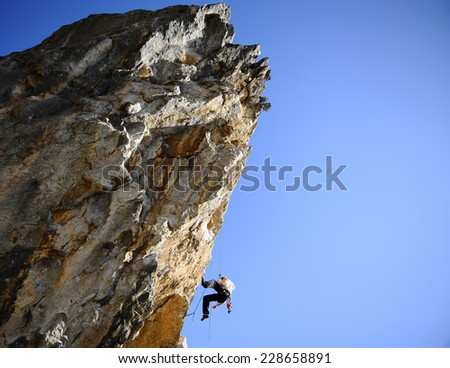 climber climbing on a rock with a negative slope. - stock photo