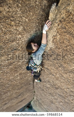 Climber clings to the side of an overhanging rock face in Joshua Tree National Park. - stock photo