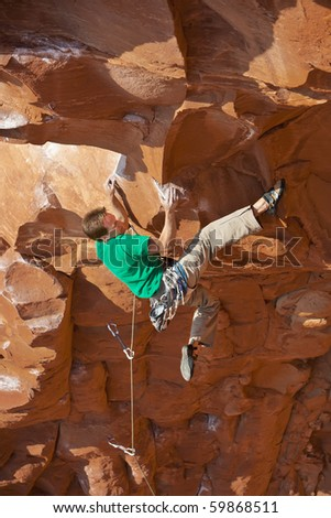 Climber clings to the side of an overhanging rock face in Sedona, AZ. - stock photo