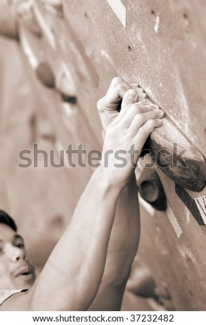 climber concentrating on the next move, focus on the hands - stock photo