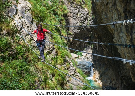 Climber Cross Gorge on a Rope Bridge