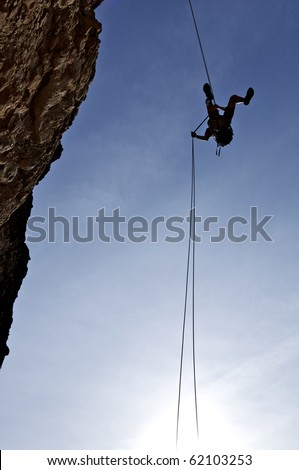 climber descending with the technique of rappelling - stock photo