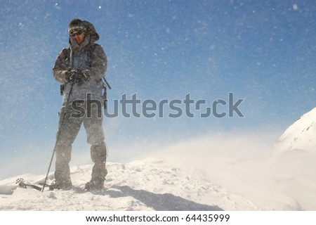 Climber facing wind and snow during trekking on top of Retezat Mountains, Romania - stock photo