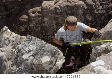 Climber goes down into a crack. Shot in Jonkershoek nature reserve, Stellenbosch, Western Cape, South Africa. - stock photo
