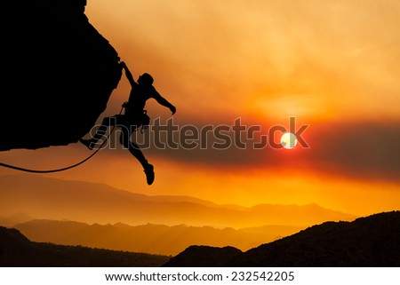 Climber gripping the edge of a cliff. - stock photo