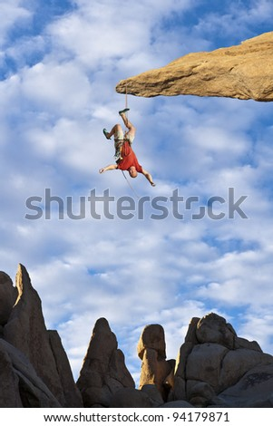 Climber in trouble at the end of his rope. - stock photo