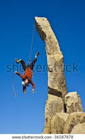 Climber in trouble clinging to a rope for dear life in The Sierra Nevada Mountains, California. - stock photo