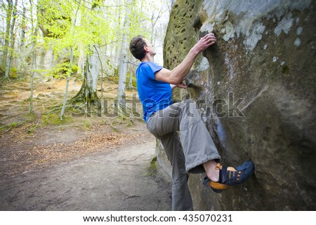 Climber is bouldering on the rocks in the forest.