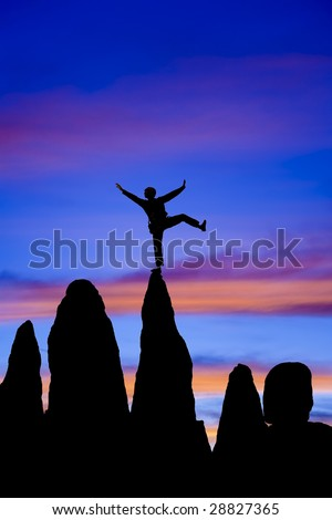Climber  is silhouetted on the summit of a rock spire doing a one leg stand, in the Sierra Nevada Mountains, California, on a summer day. - stock photo