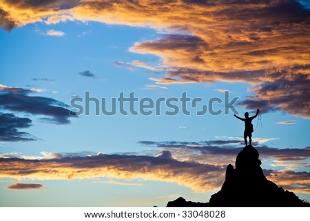Climber  is silhouetted on the summit of a rock spire in the Sierra Nevada Mountains, California, on a summer day. - stock photo
