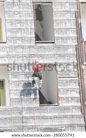 climber of firefighters during exercise at fire station - stock photo