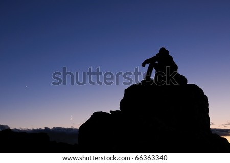 Climber on a mountain peak in the Rocky Mountains of Colorado, under a night sky. - stock photo