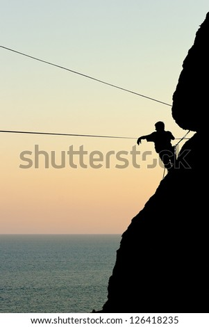 climber on a rock preparing the rope for highlining against the sea at sunset - stock photo