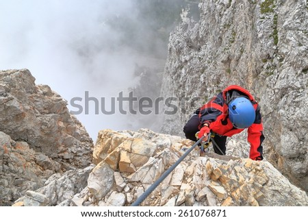 "Climber on exposed ridge above the clouds on via ferrata ""Punta Ana"", Tofana massif, Dolomite Alps, Italy - stock photo"