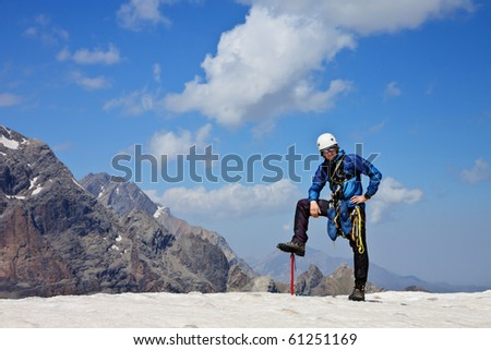 climber on mountain summit with blue cloudy sky - stock photo