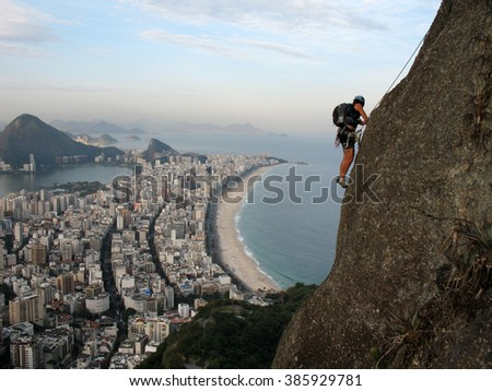 Climber on rock wall with Rio de Janeiro beach on background - stock photo