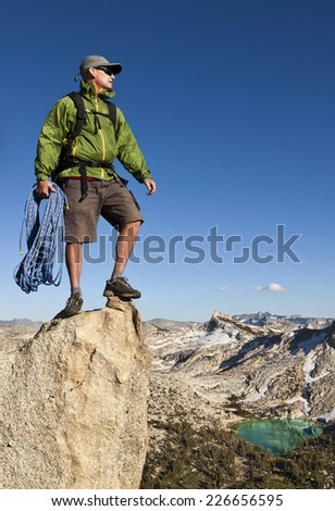 Climber on the edge of a challenging cliff. - stock photo