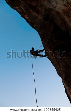 Climber on the rock against the blue sky - stock photo