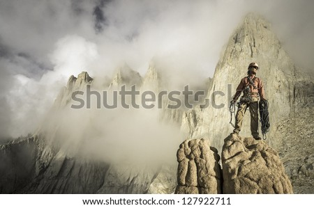 Climber on the summit after a challenging ascent. - stock photo