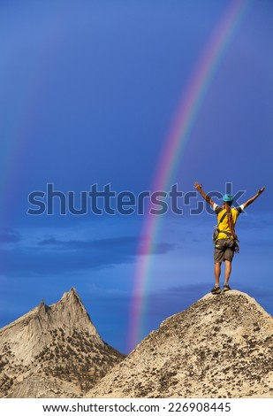 Climber on the summit of a challenging cliff. - stock photo