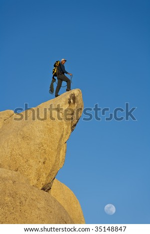 Climber on the summit of a rock spire after a successful ascent, in the Sierra Nevada Mountains, California. - stock photo