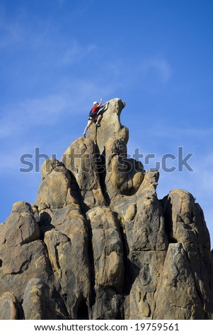 Climber on the summit of a rock spire in the Sierra Nevada Mountains, California, on a summer day.