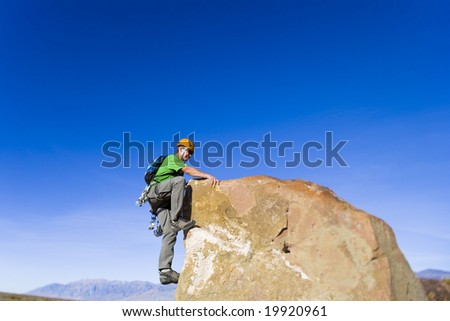 Climber on the summit of a rock spire in the Sierra Nevada Mountains, California, on a sunny day. - stock photo