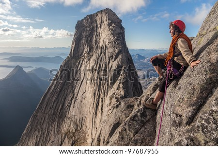 climber on the top and big rock in background - stock photo