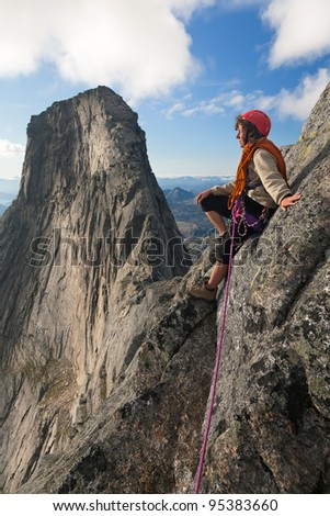 climber on the top and big rock in the background - stock photo