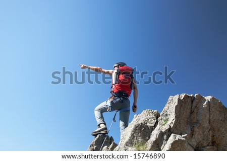 Climber pointing his hand, on a stone at the top of his route, over a deep blue sky.