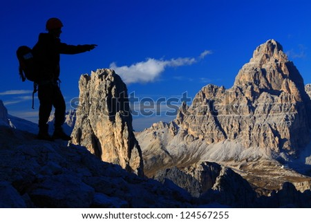 Climber pointing to the outstanding mountain view, Cadini di Misurina, Dolomite Alps, Italy - stock photo
