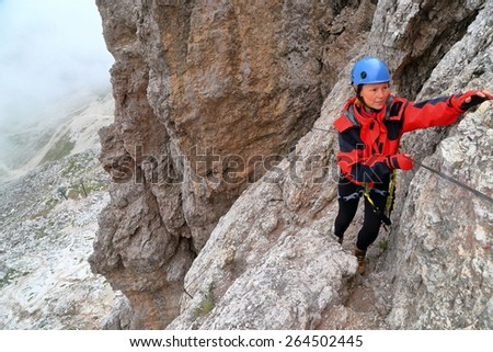 Climber progressing along protection cable of via ferrata route, Dolomite Alps, Italy - stock photo