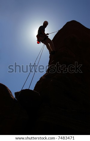 Climber rapelling from the top of a climb - stock photo